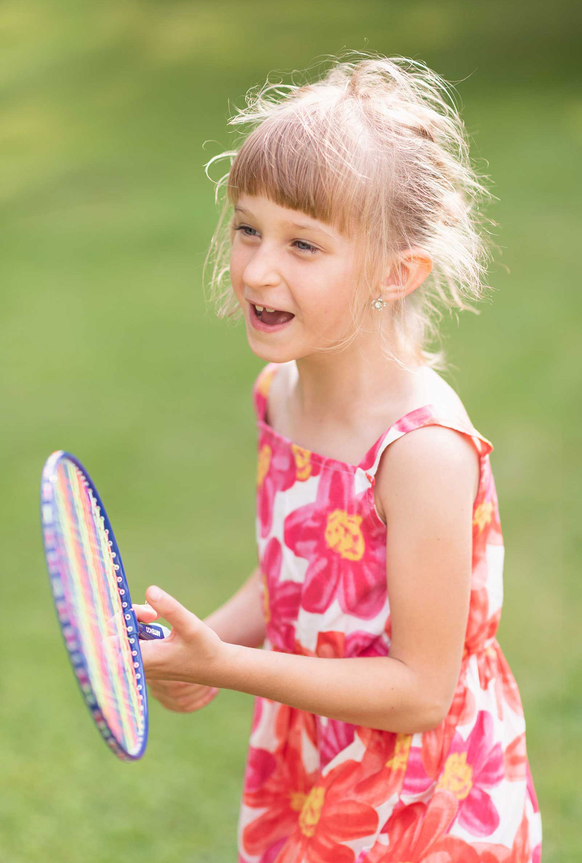 Young girl smiling with badminton racket in pink floral dress