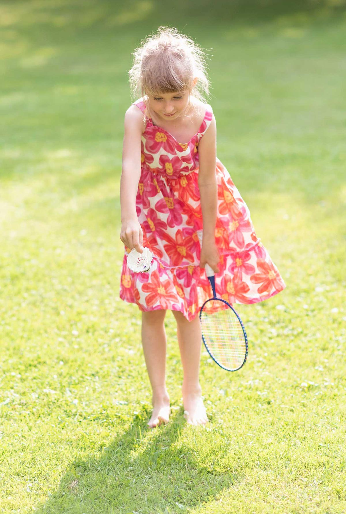 Young girl playing badminton in pink floral dress