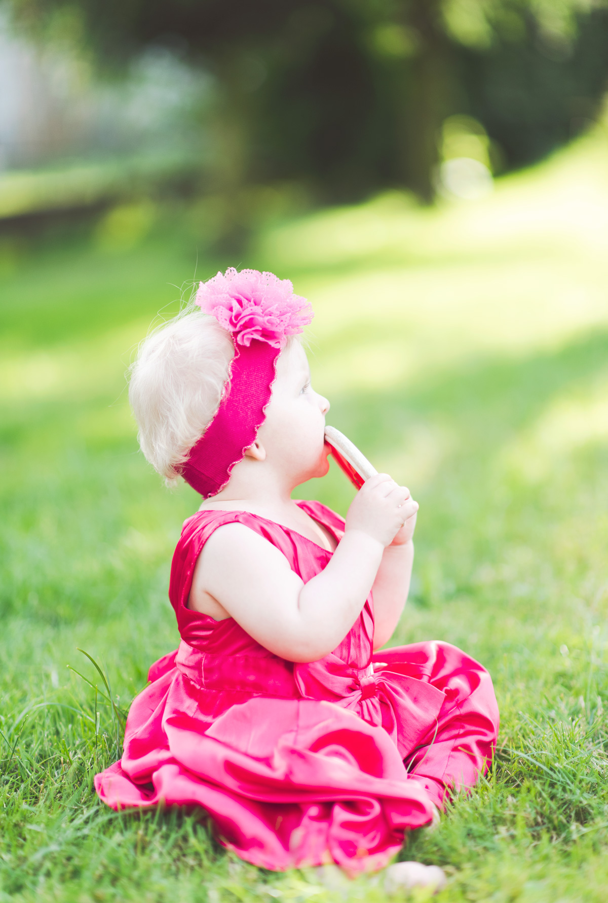 Baby girl in pink dress sitting on the grass in the garden