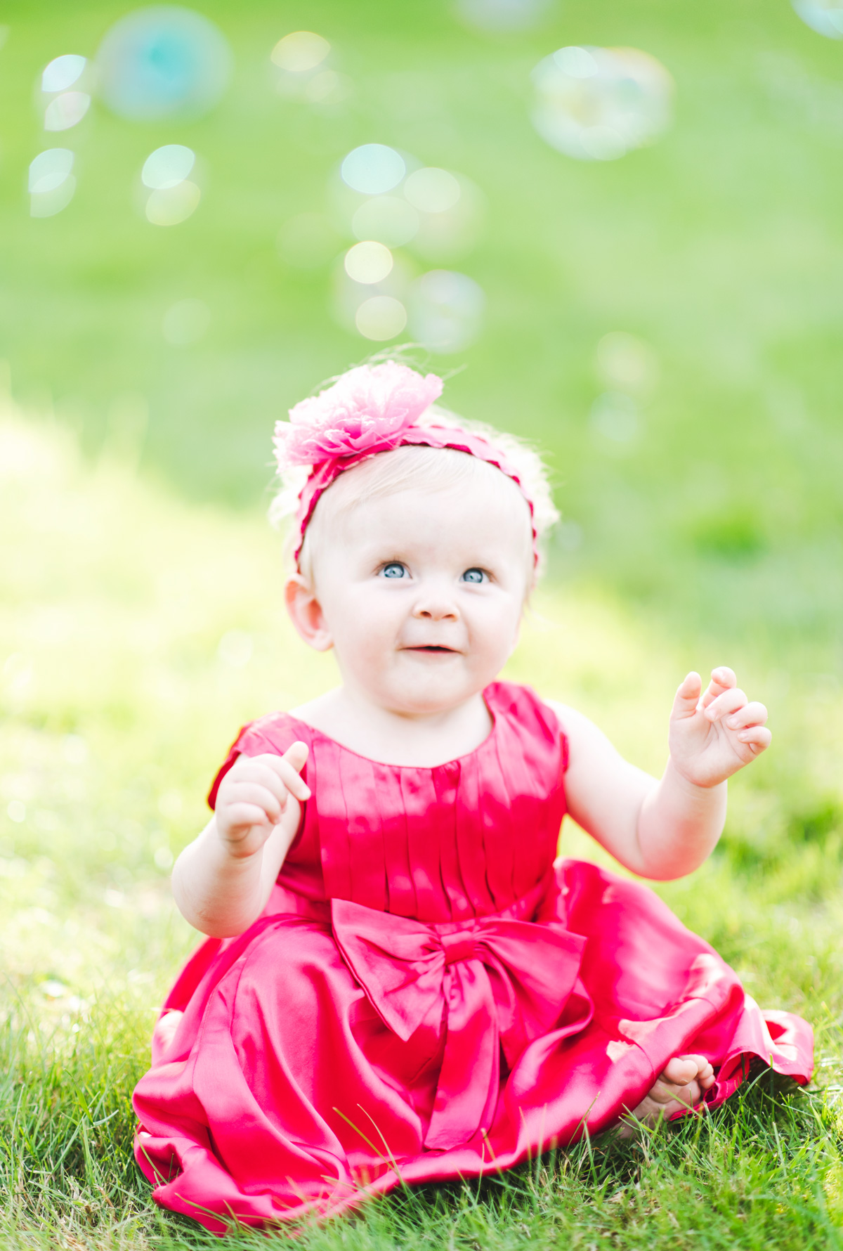 Baby girl in pink dress sitting on the grass smiling and playing with bubbles