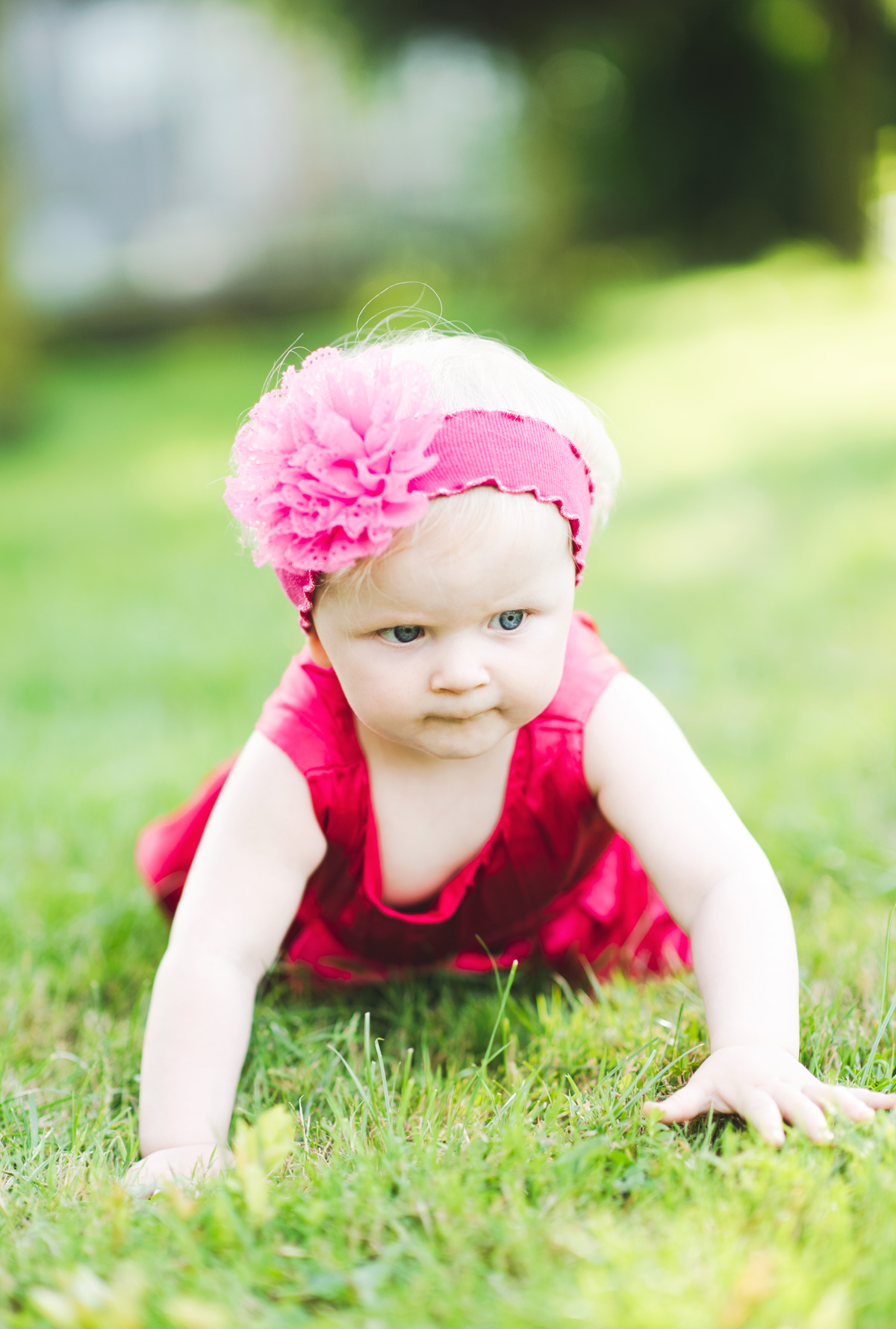Baby girl in pink dress crawling on the grass in the garden