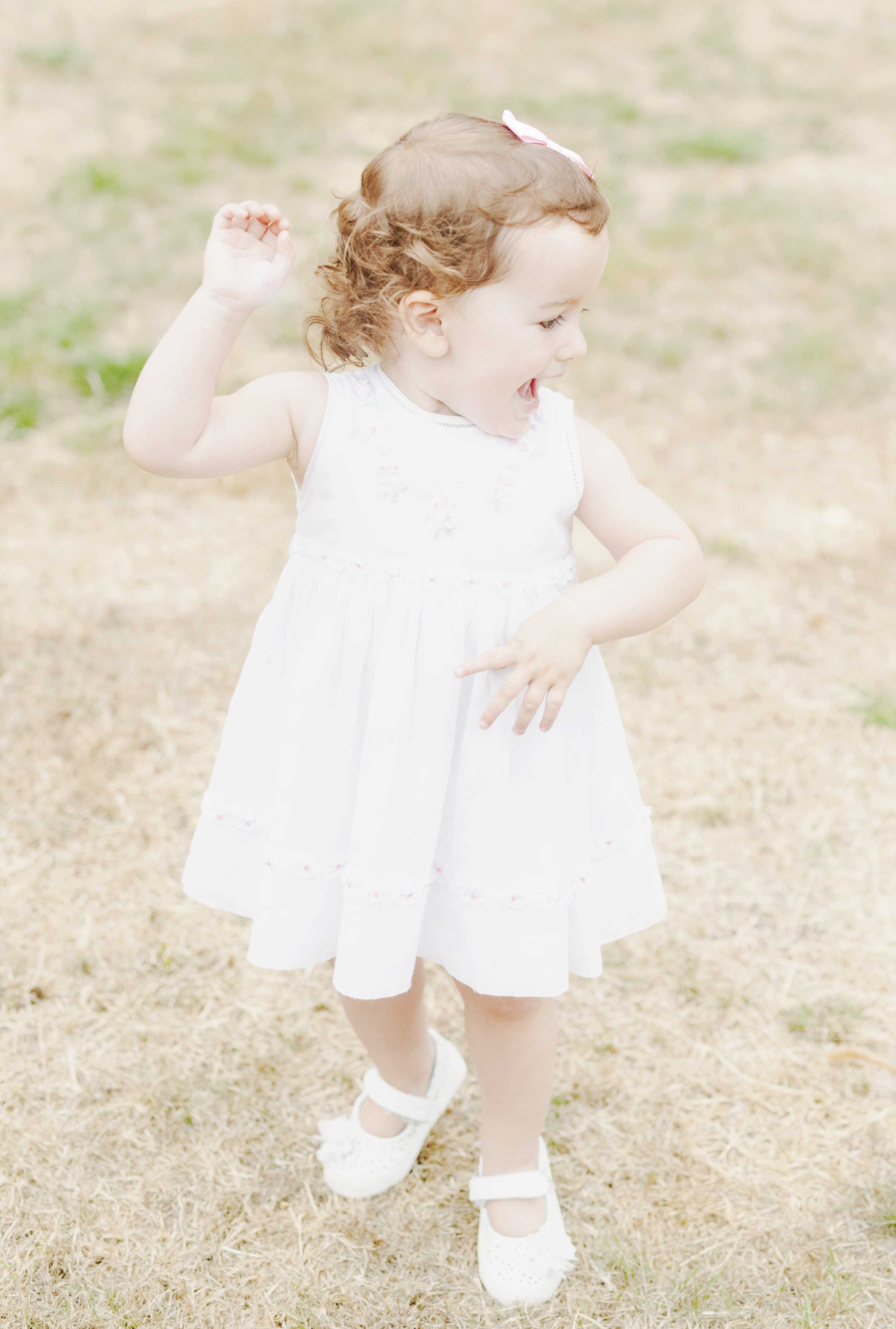 Baby girl posing in white dress in Canizaro Park, Wimbledon, London