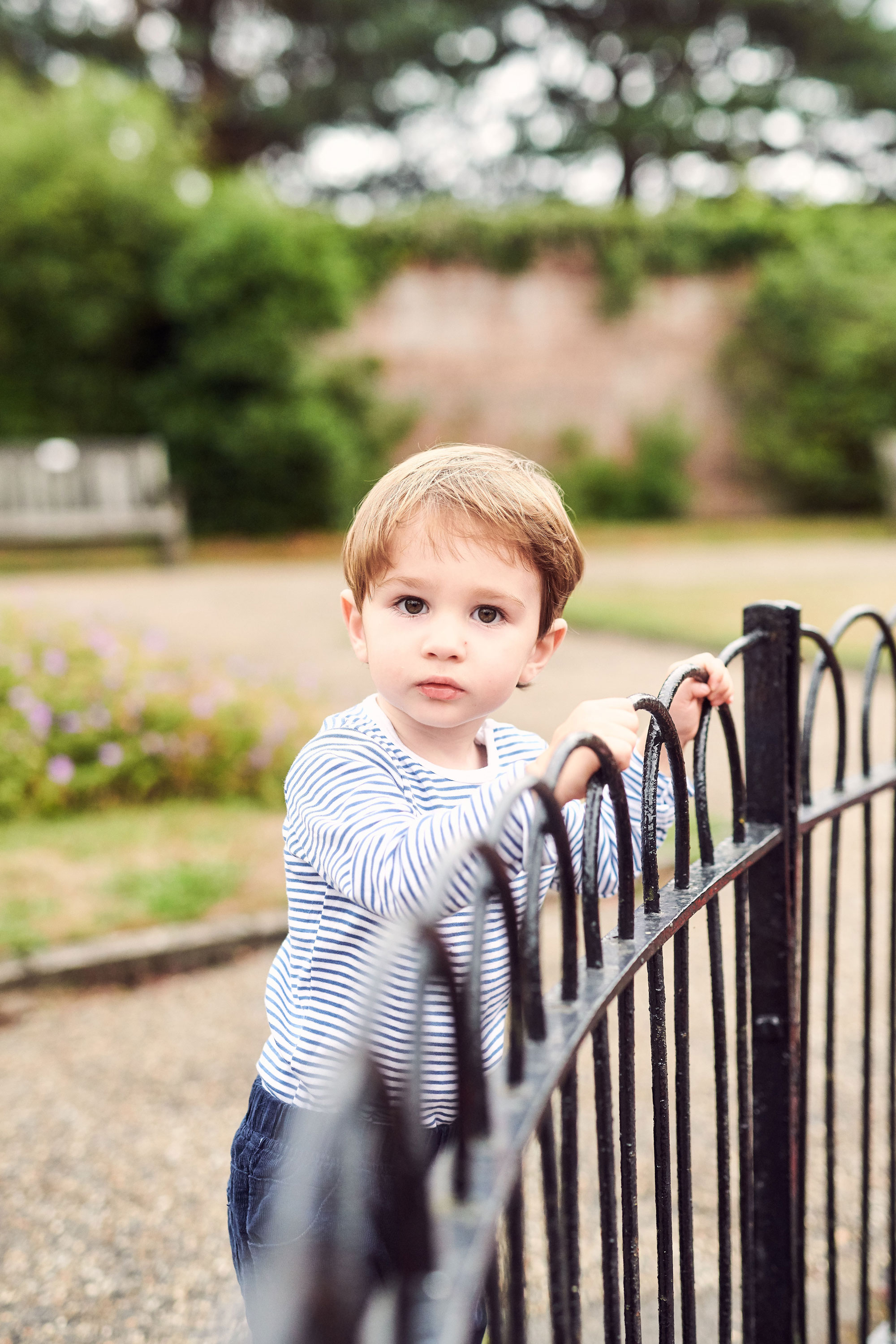 toddler boy in stripy top and blue trousers in the park
