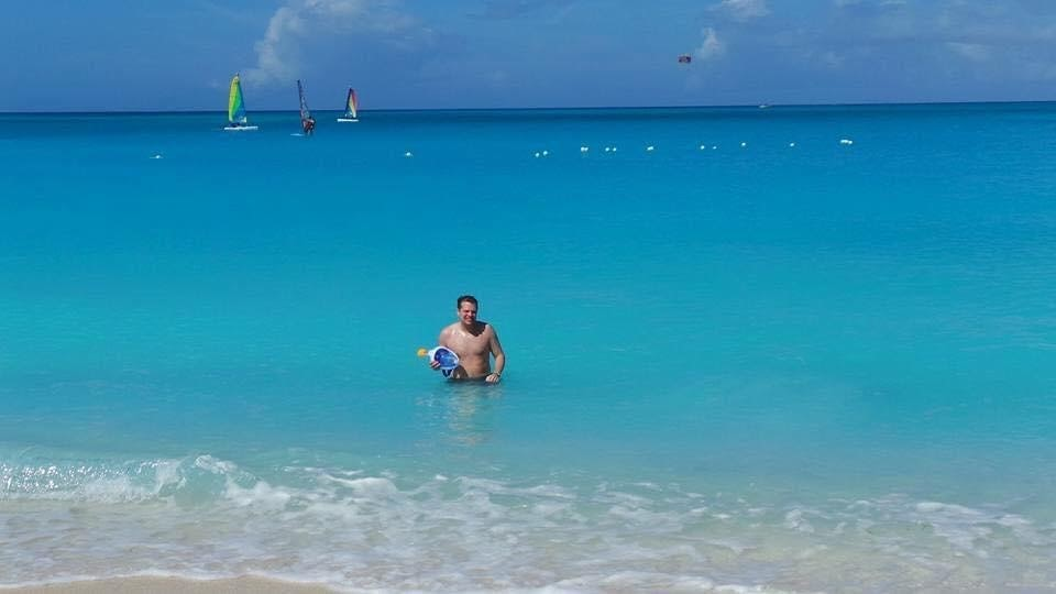 Sarah's husband testing out their new snorkeling masks in the clear, blue ocean in Turks and Caicos