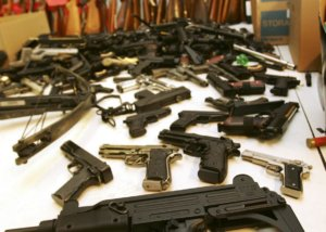 a table full of handguns and rifles