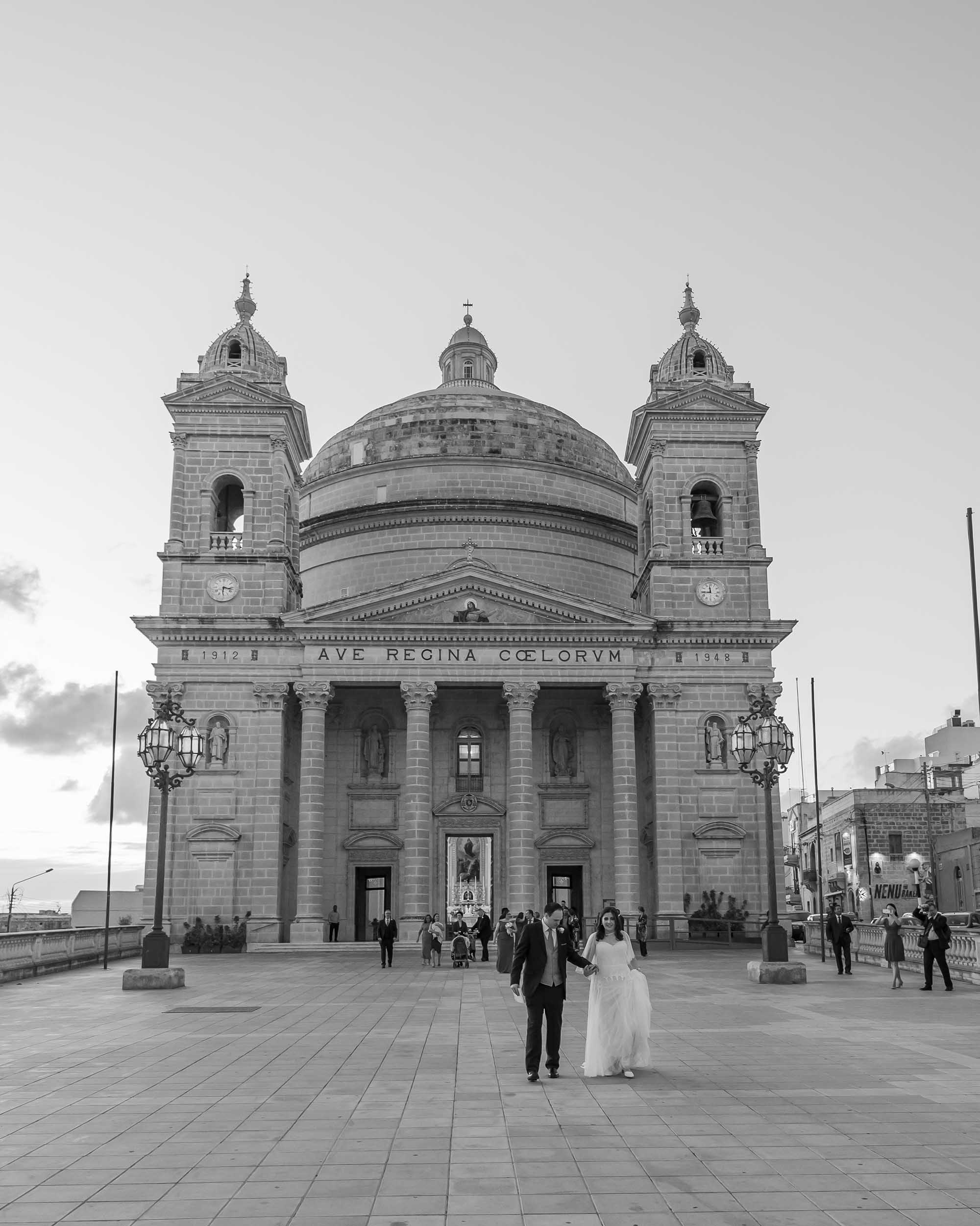 Candid photo showing the newly-wedded husband and wife going away from the church in Imgarr, Malta