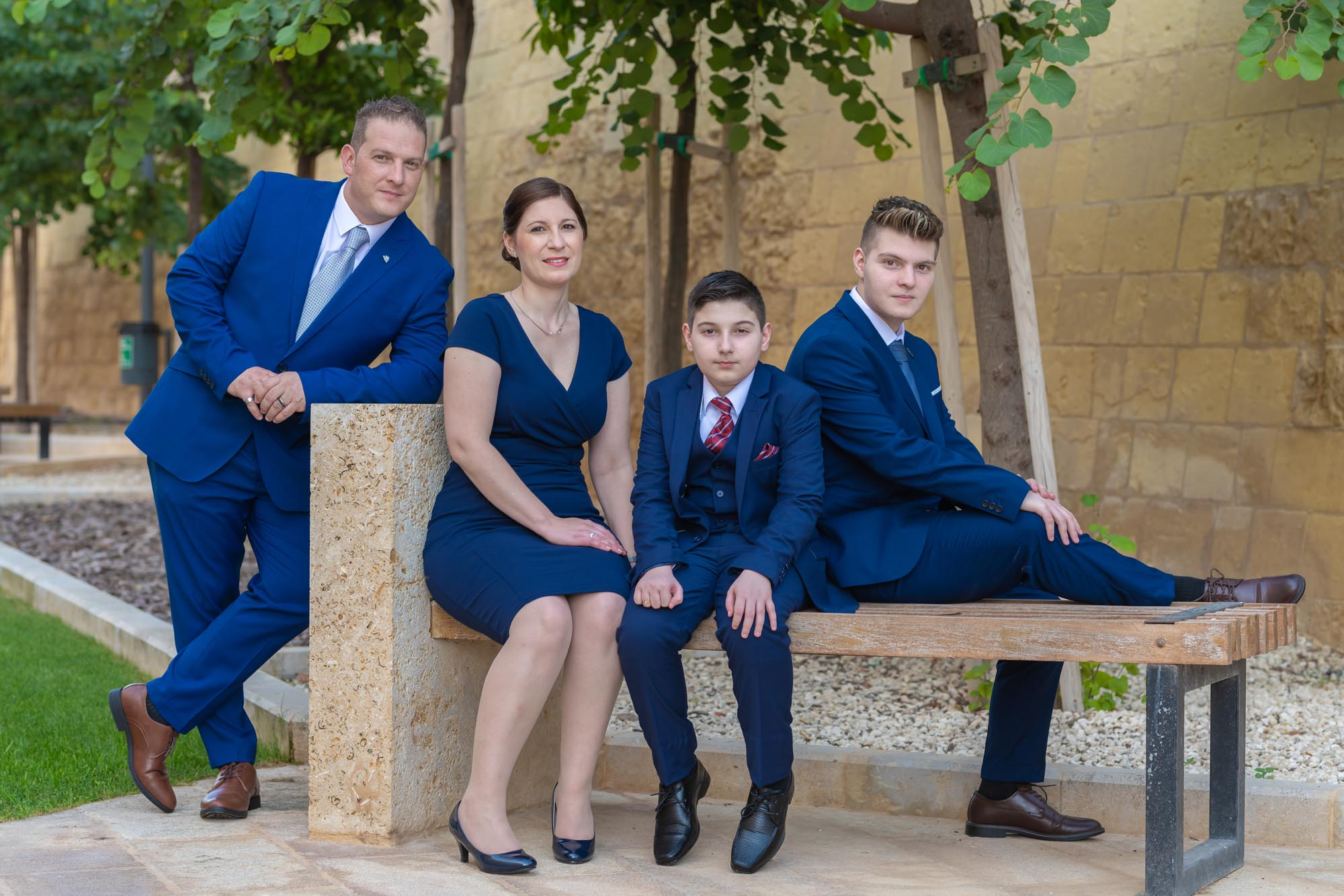 Family with Confirmation son smiling on park bench in Victoria Gozo