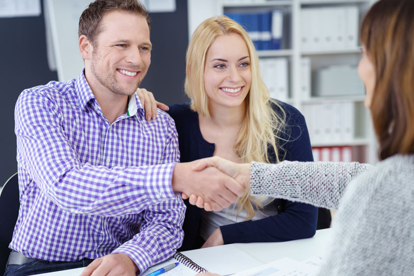 Couple talking to a conveyancer for a property sale