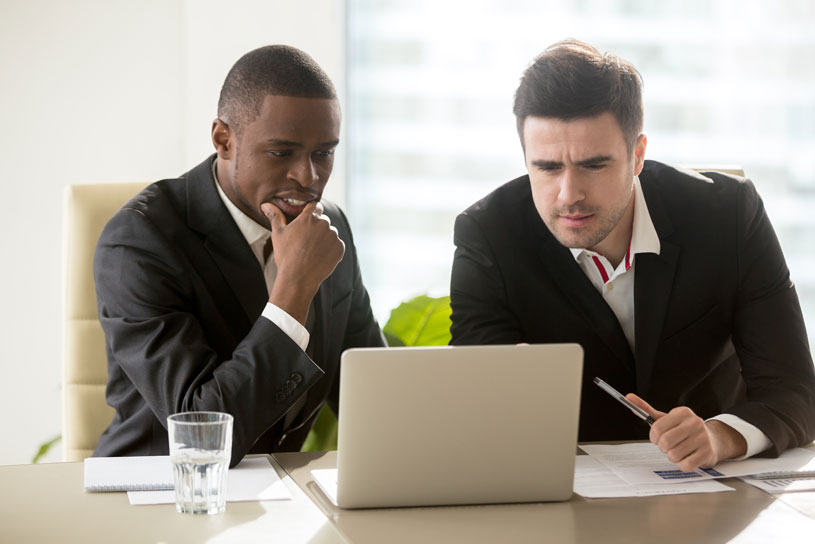 Two men looking online for the costs of conveyancing online