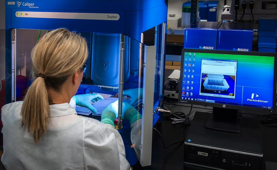 This image depicted a Centers for Disease Control and Prevention (CDC) scientist interacting with her Caliper LifeSciences' Zephyr Molecular Biology Workstation
