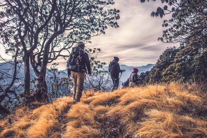 a group of people hiking with rucksacks on a hill with beautiful scenery
