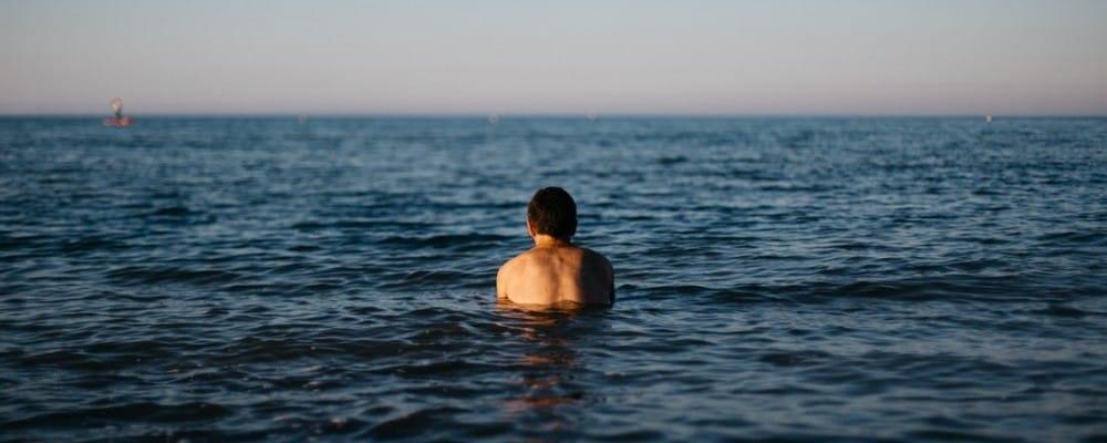 man swimming in ocean of open water