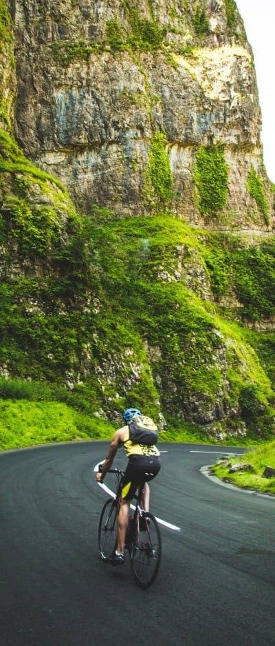 cyclist on a bend in the road with moss covered rocks around him