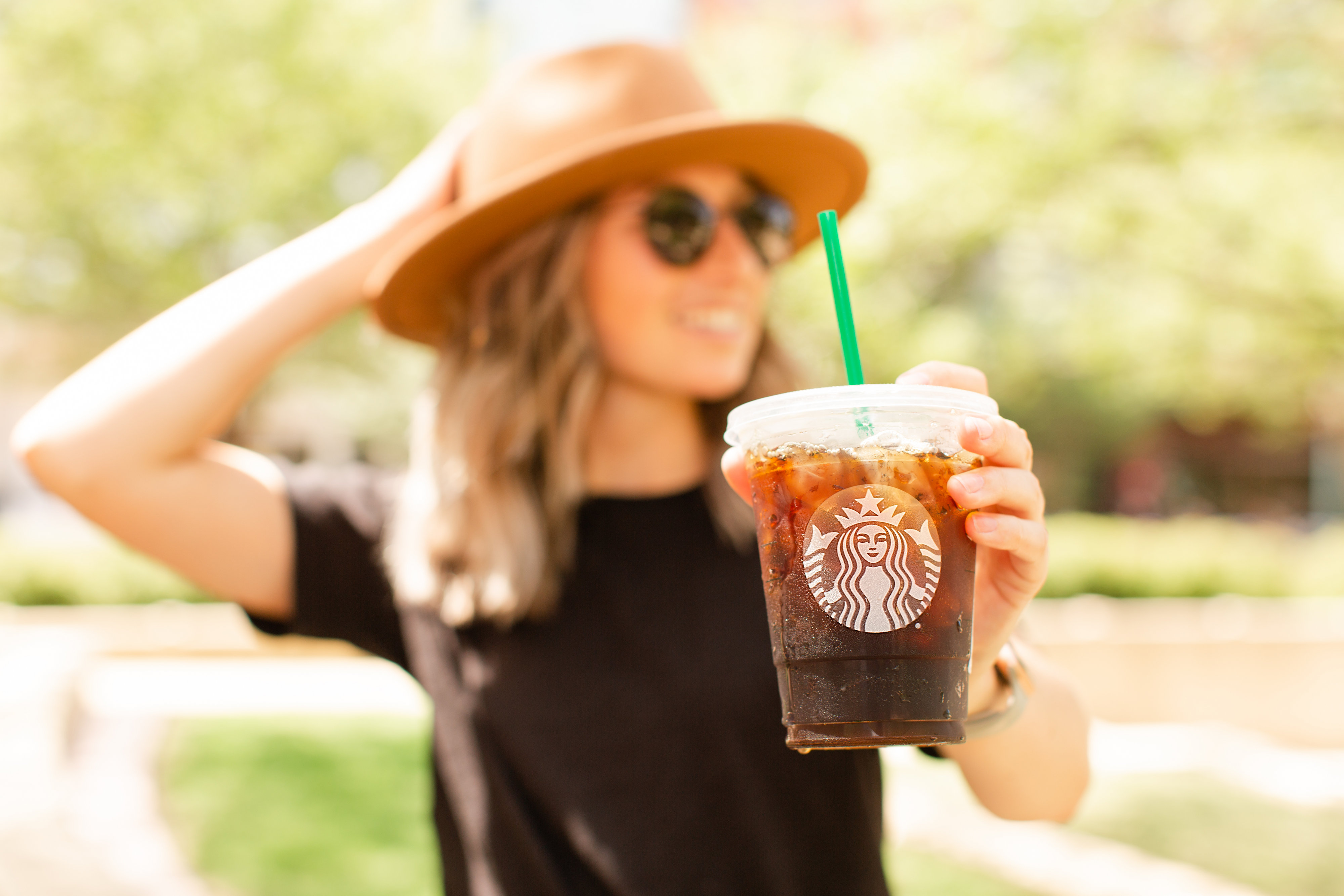 Starbucks brand photograph with young woman holding iced coffee in hand