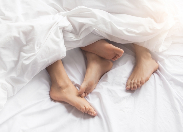 couples_feet_showing_from_under_bed_covers