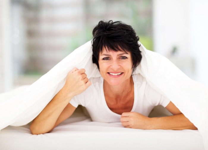 middle_aged_women_looking_up_smiling_under_bed_covers