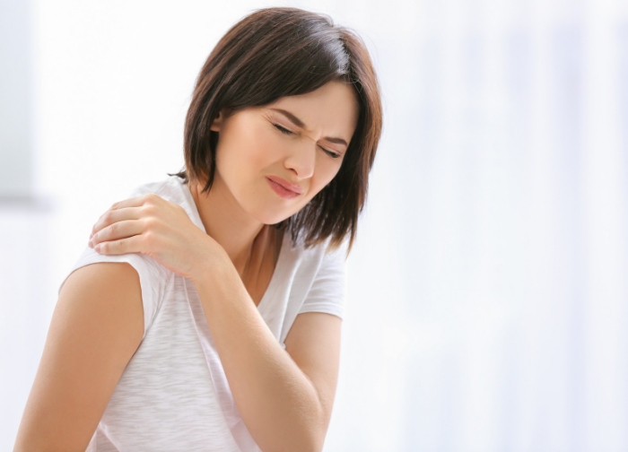 young_woman_suffering_holding_shoulder_at_home