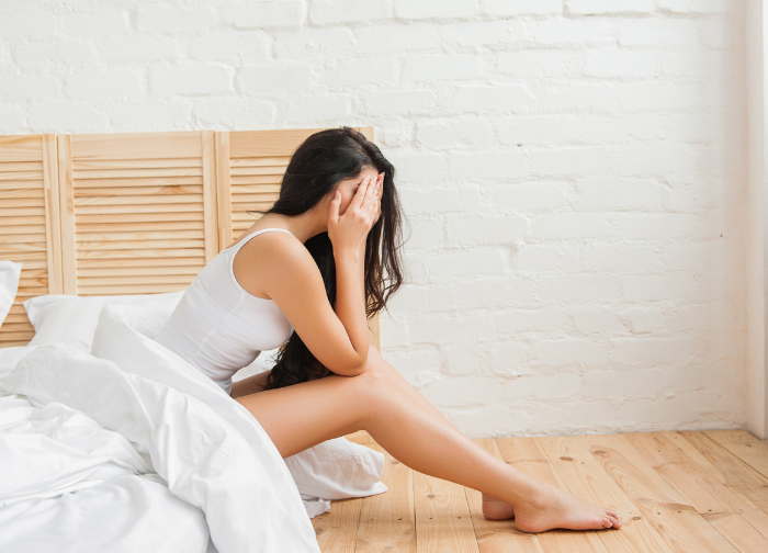 Frustrated and sad young women with hands over face sitting on edge of bed