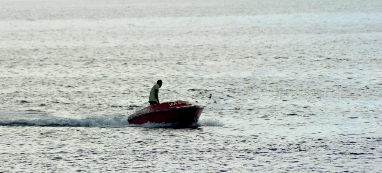 Man on a speed boat at Corbyn's Cove beach, water sports