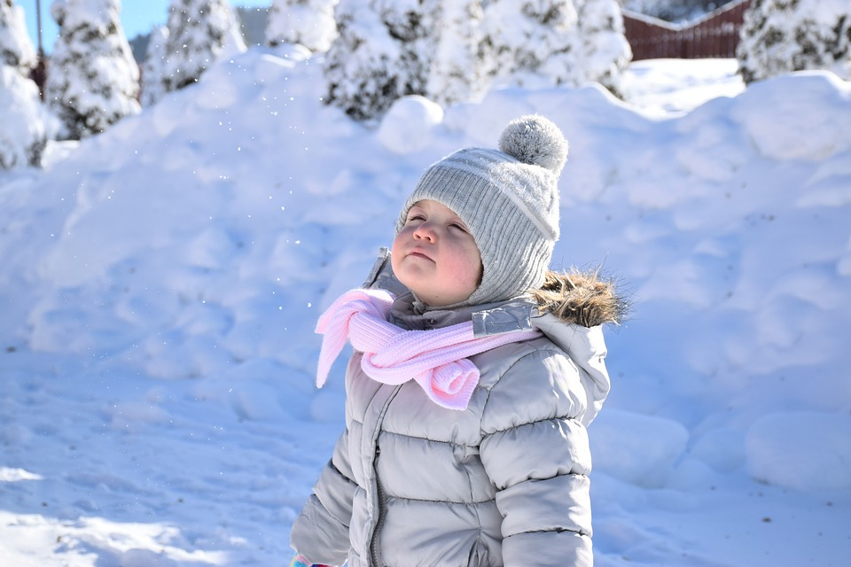 toddler in the snow with a snow hat