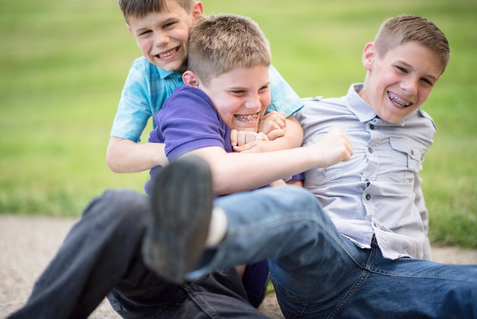 three young boys play fighting