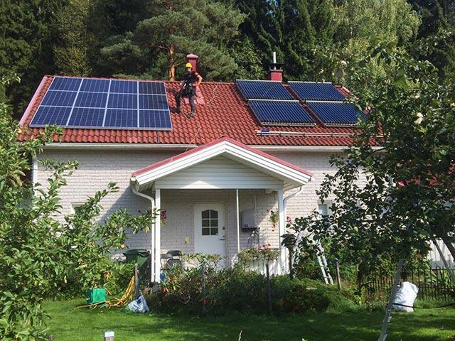 asentaja asentamassa aurinkopaneeleita