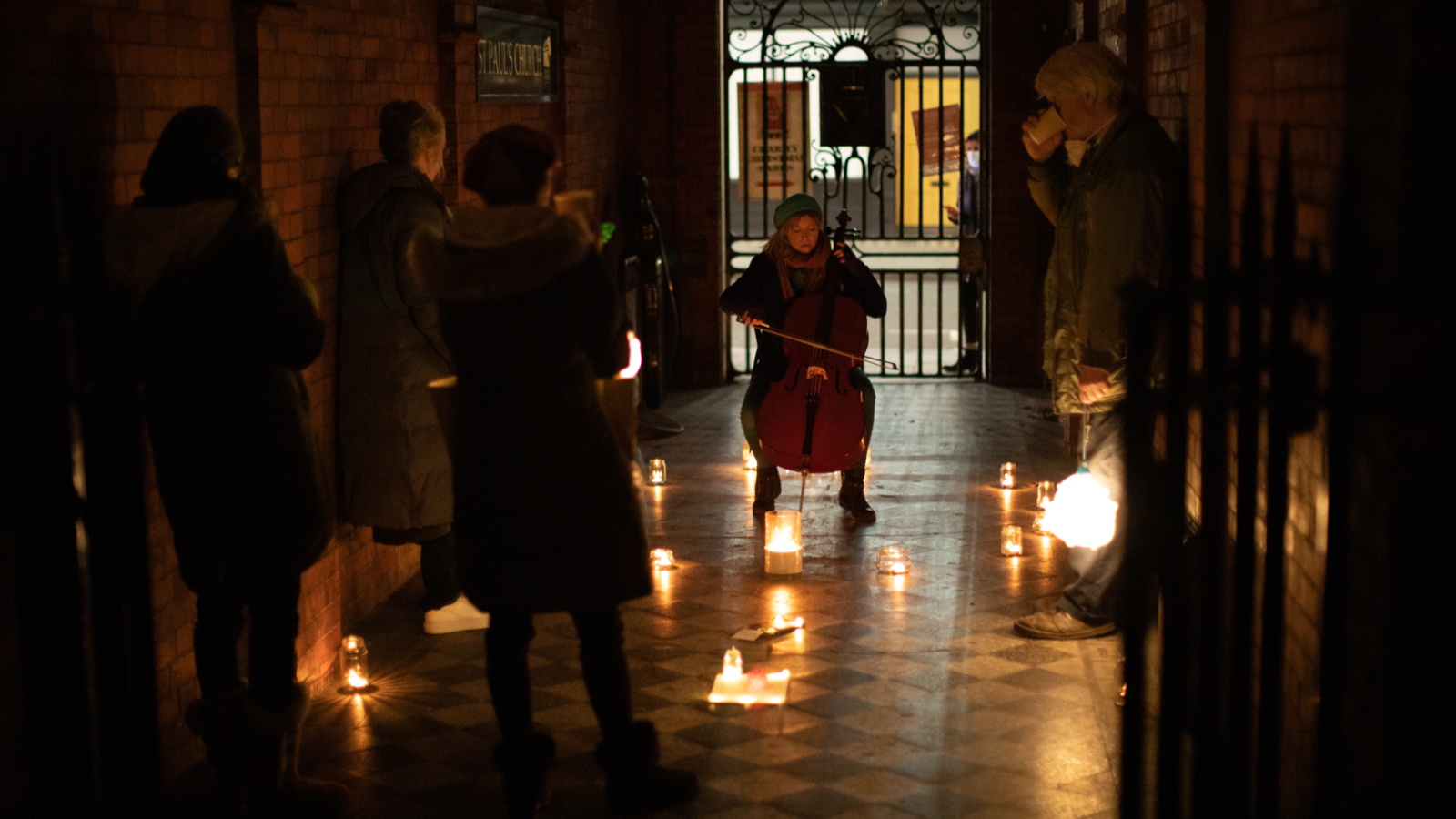 We are in a dark alley with red brick walls and black and white tiles. A young woman sits wrapped in winter clothes playing the cello surrounded by candles which glisten on the tiled floor. A small socially distanced audience watch her play. At the other end of the alley is an iron gate and a figure can be seen watching through the gate