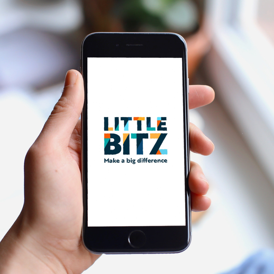Photo of a hand holding an iPhone with the Little Bitz logo.