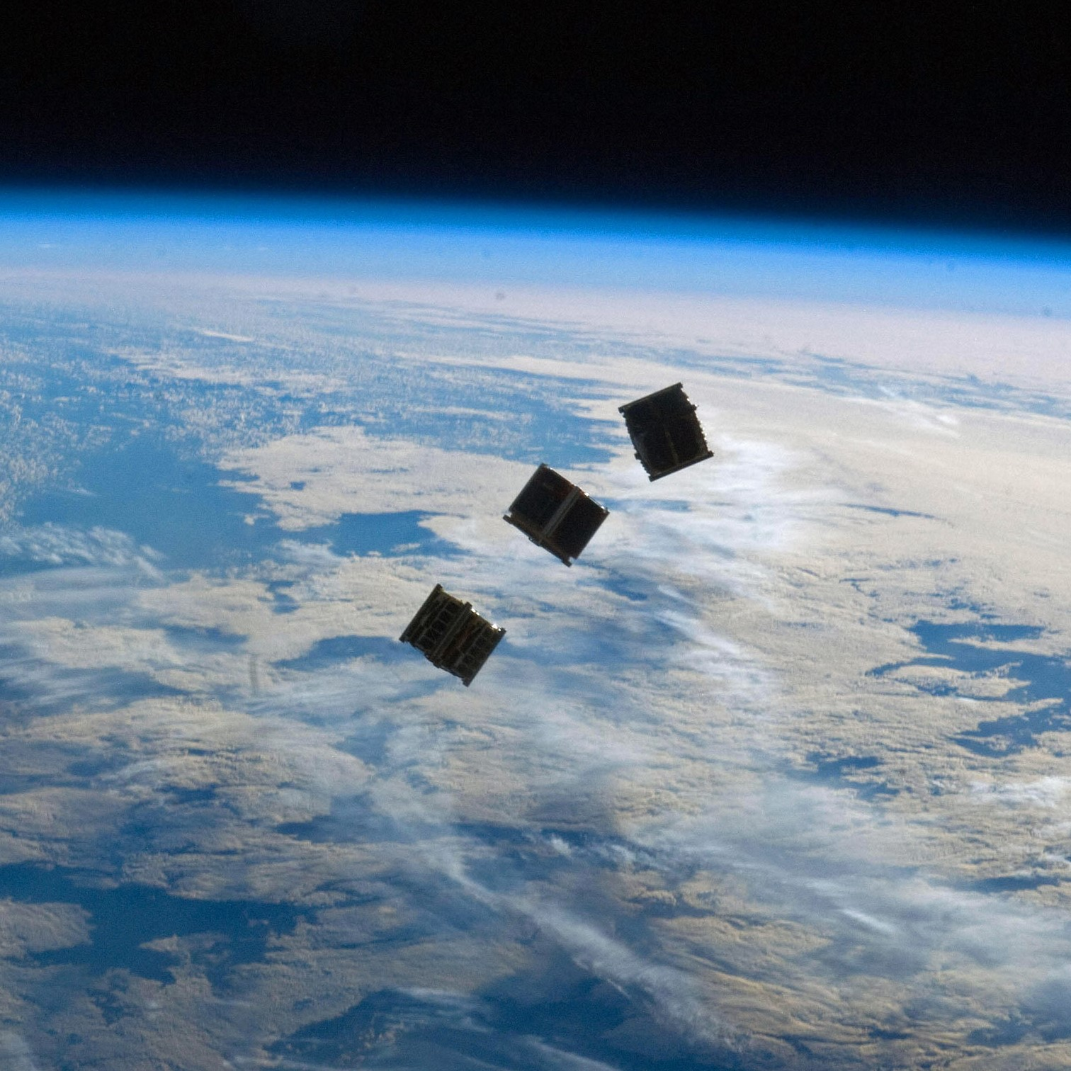 three cubesats above the Earth