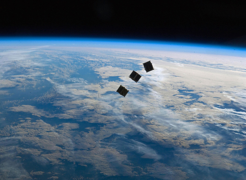 Three nanosatellites above the Earth
