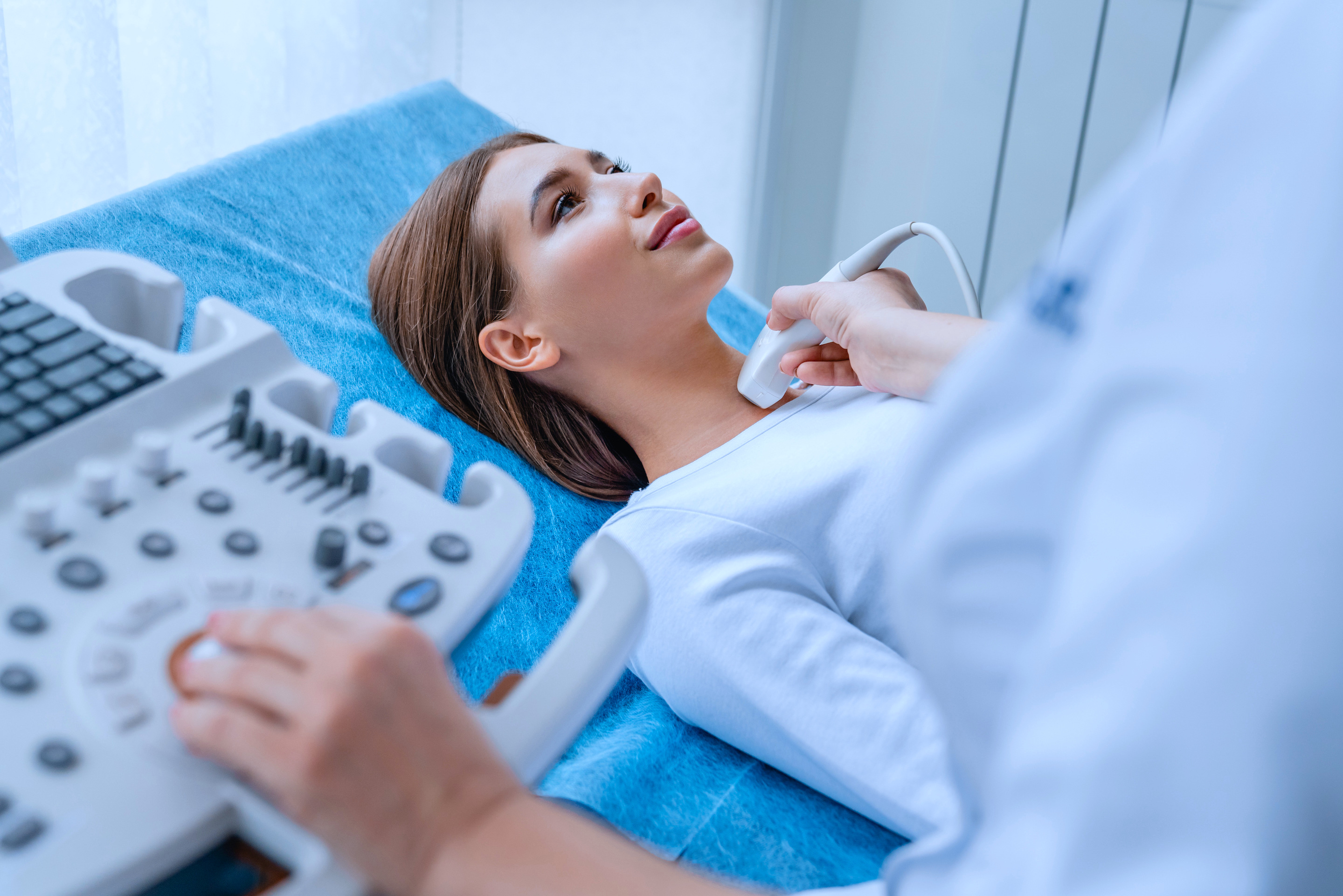 Woman on bed receiving ultrasound.