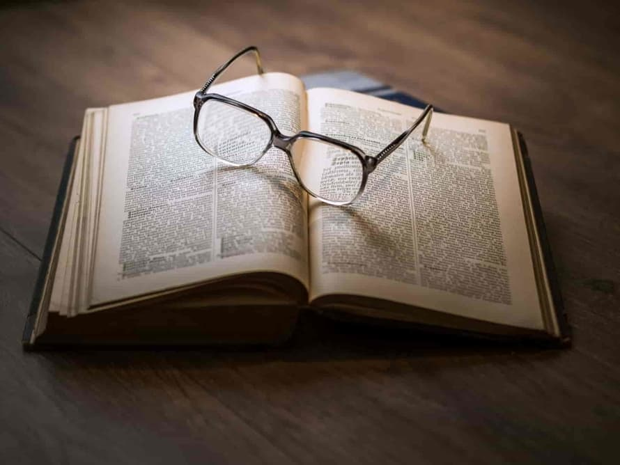 book open with glasses on it