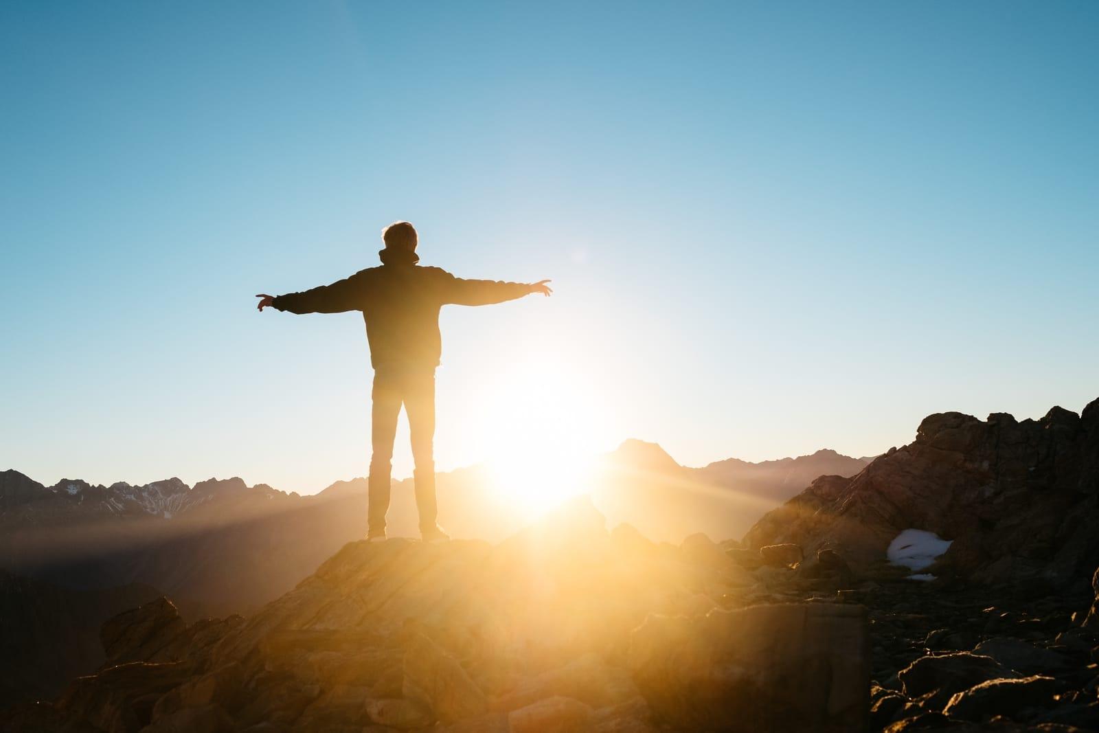 man watching sunrise from boulder