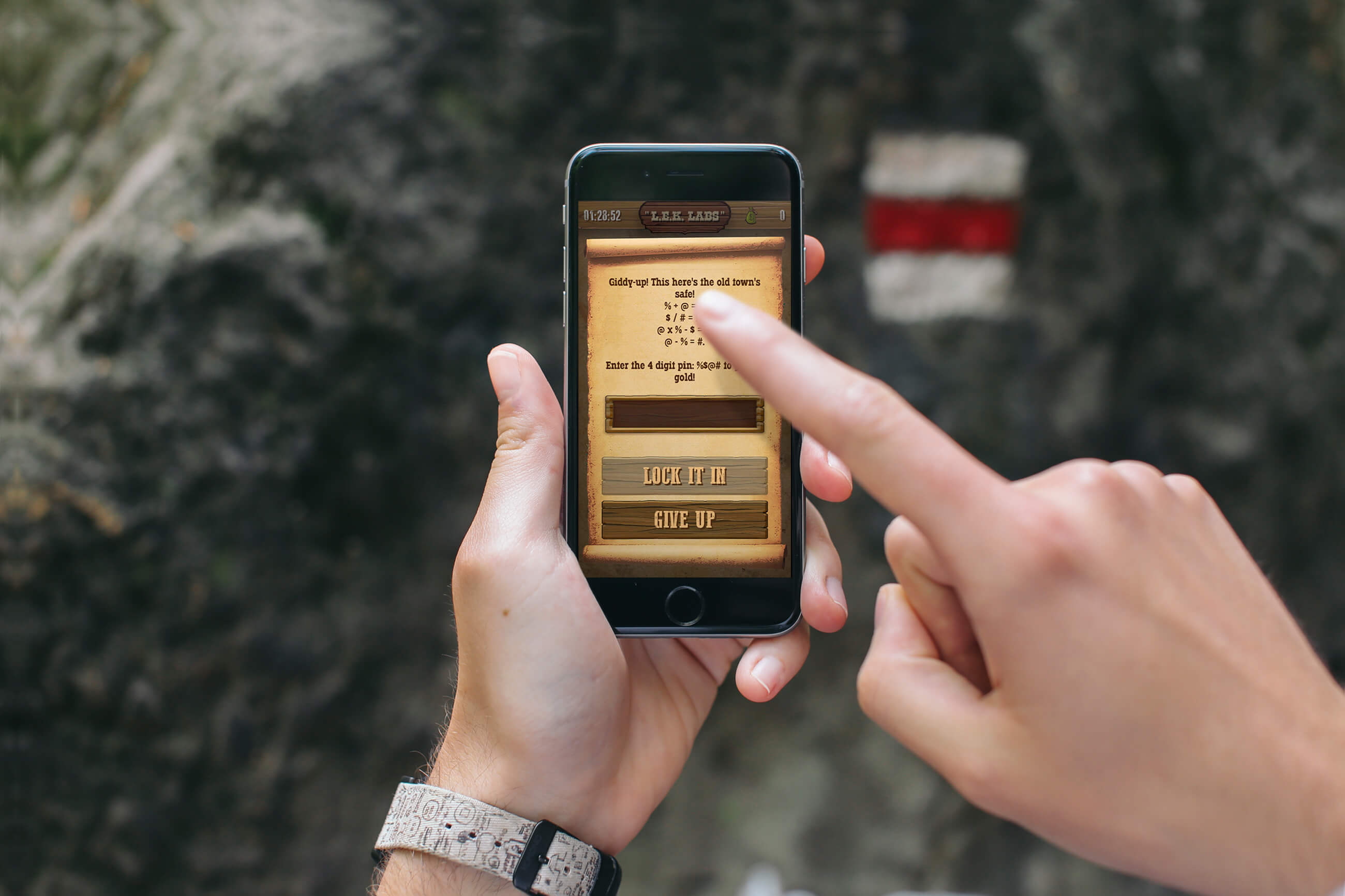 An image of someone holding a phone and touching the LEK Labs Wild West Adventure app