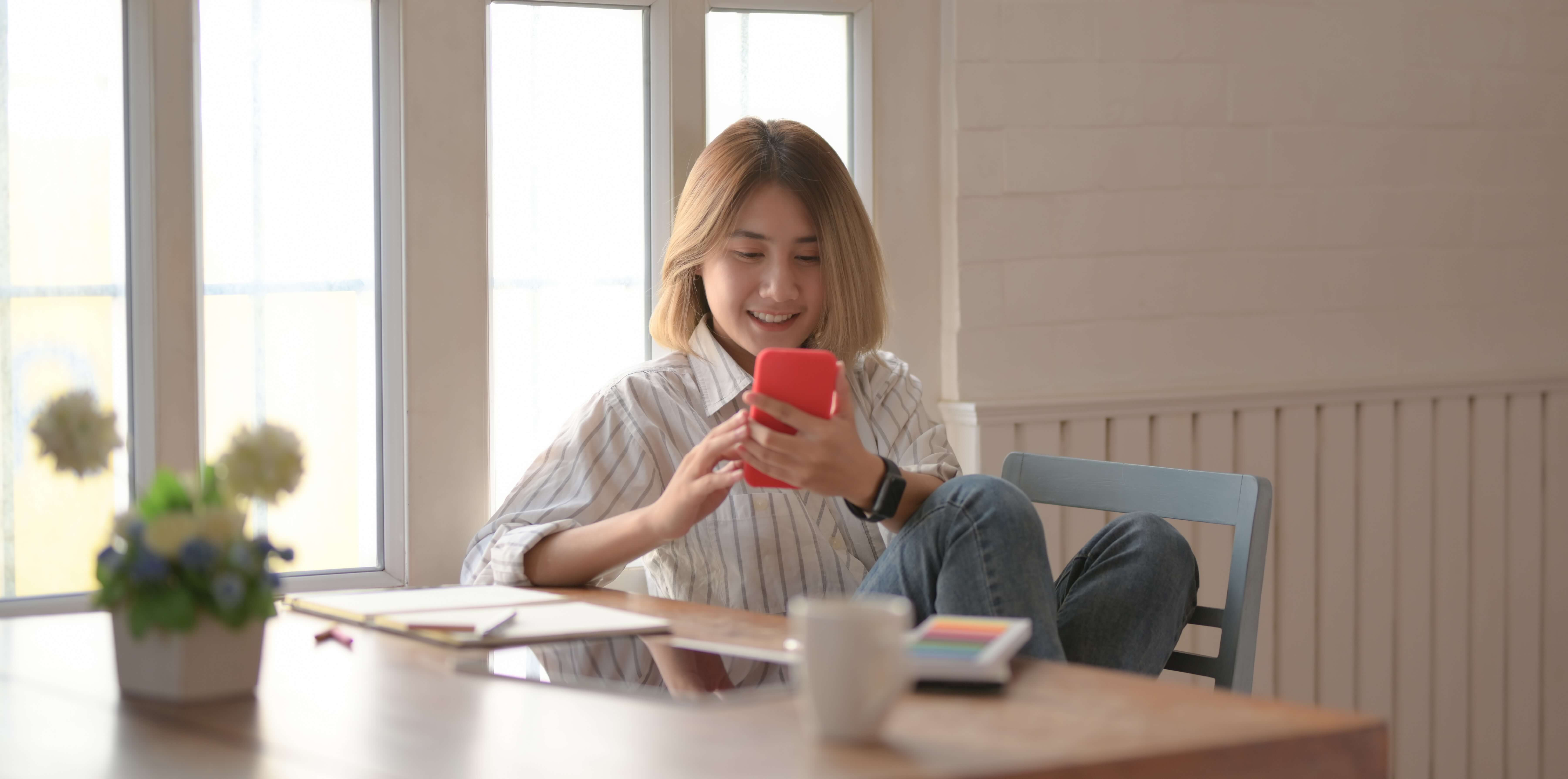 Photograph of young woman playing games on her mobile phone. KangaZoo is a mobile simulation game developed by PentaQuest and Chaos Theory.