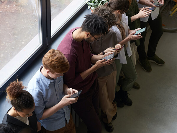 A photograph of people playing games on their mobile devices  - Chaos Theory | Serious Games Developer, Australia