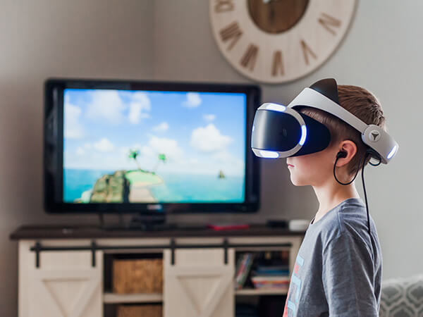 A photograph of a young boy using a virtual reality headset  - Chaos Theory | Serious Games Developer, Australia