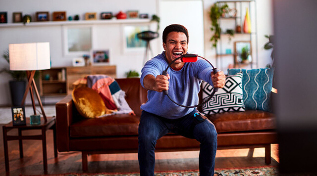 A photograph of a man playing Ringfit on a Nintendo Switch Console  - Chaos Theory | Serious Games Developer, Australia