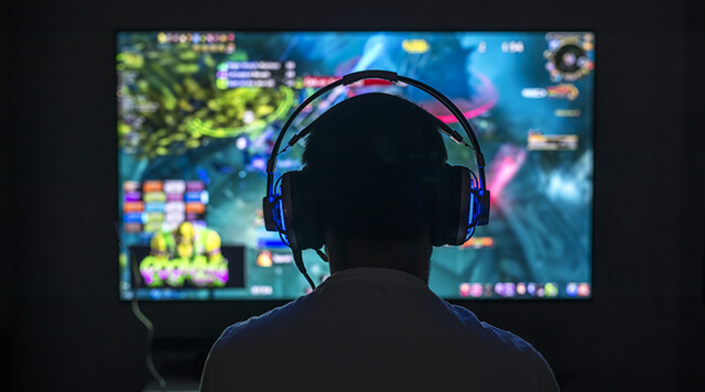 A photograph of a person playing video games with a headset on - Chaos Theory | Serious Games Developer, Australia