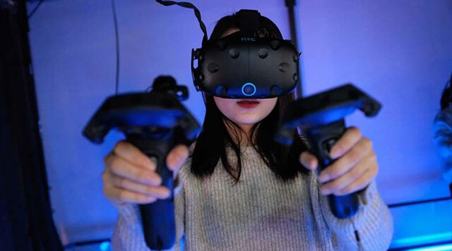 A photograph of a woman with a virtual reality headset and controllers - Chaos Theory | Serious Games Developer, Australia