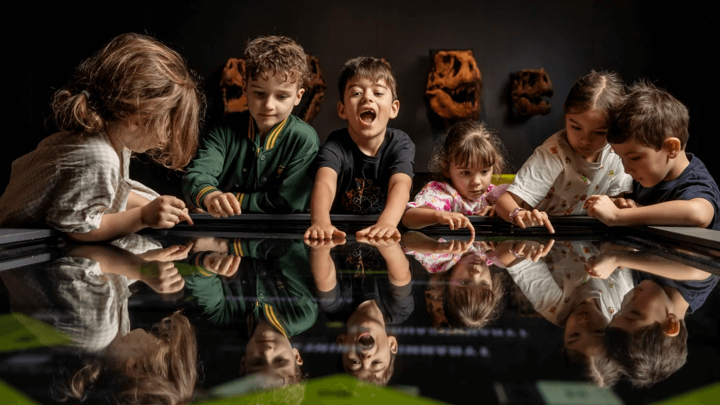 Photograph of multiple children playing on a museum touchscreen interactive table