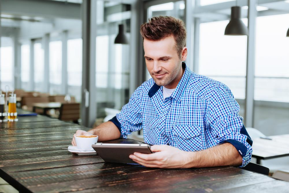 A man drinking coffee and looking at his electronic device