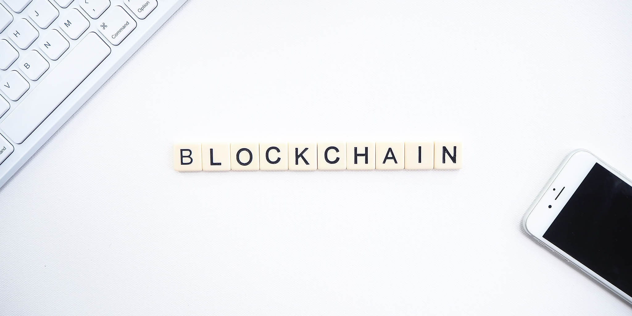 Scrabble tiles placed on a table to spell out Blockchain