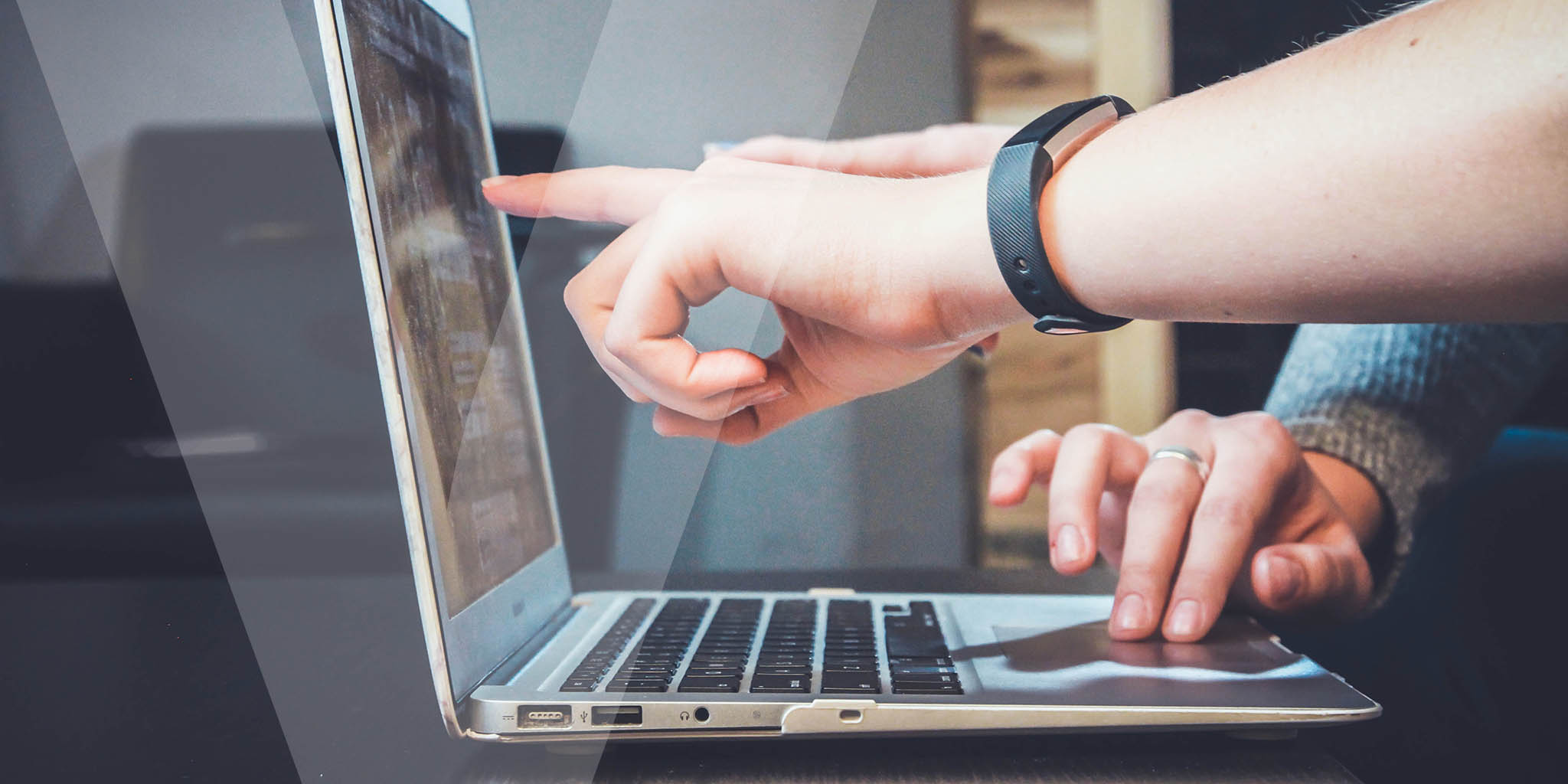 Close up image of a laptop with people pointing at the screen