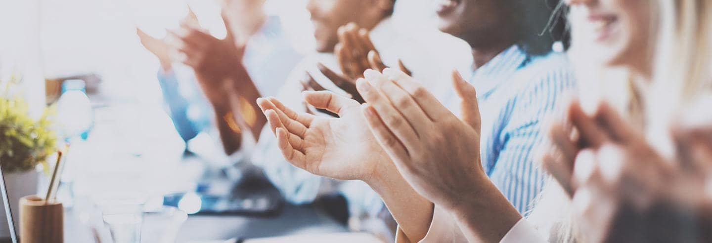 A group of people clapping together