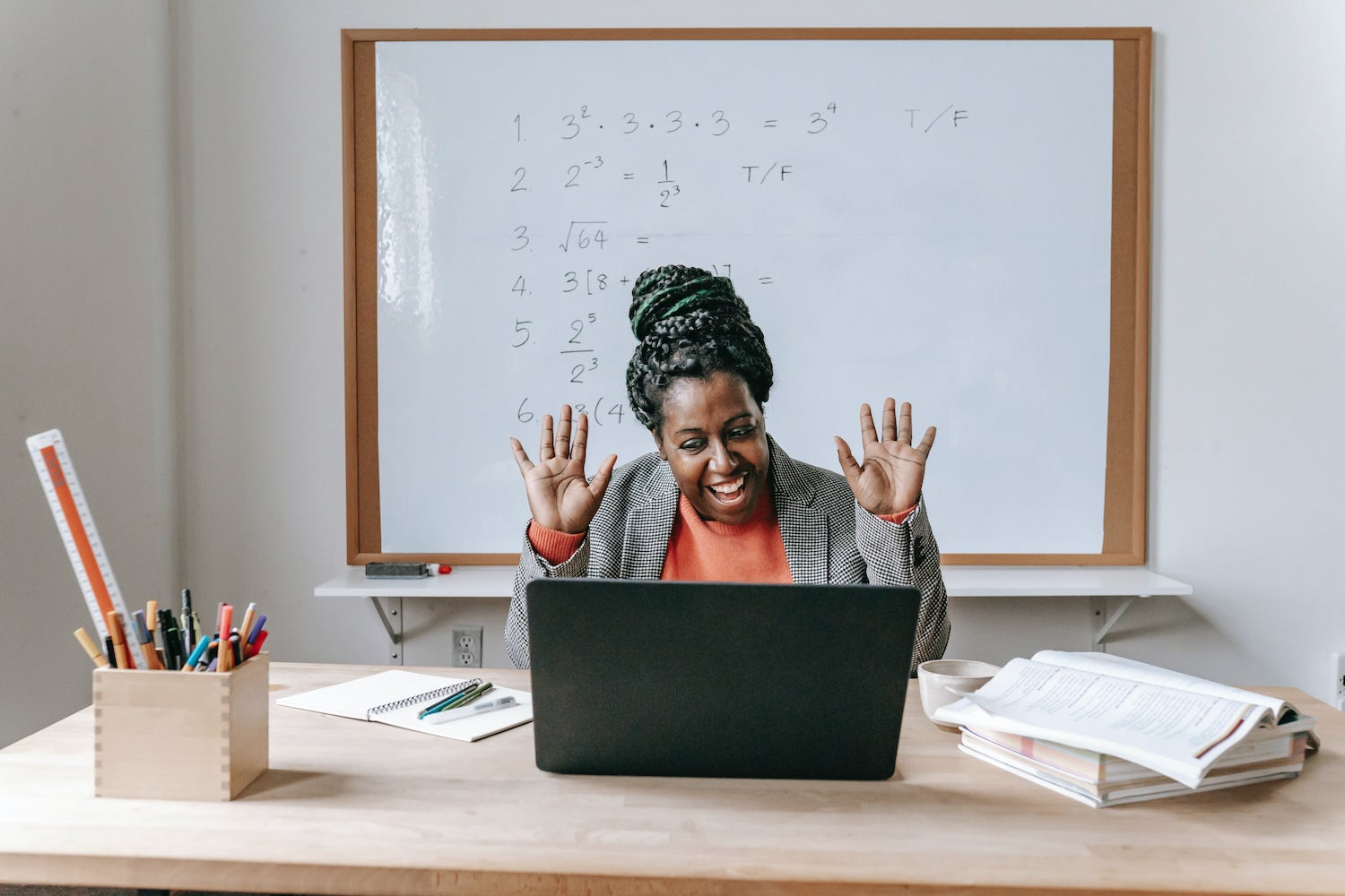 A woman on a video call with a whiteboard full of equations behind her