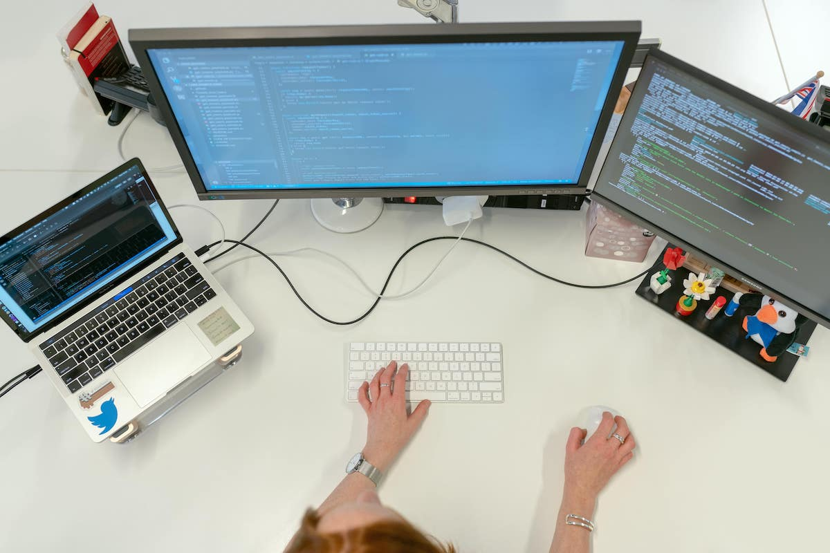 A person working at their desk with multiple monitors