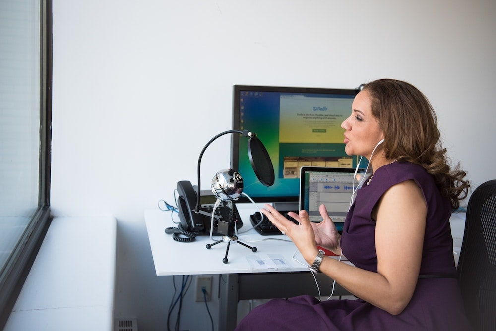 A woman speaking through a microphone and recording a podcast