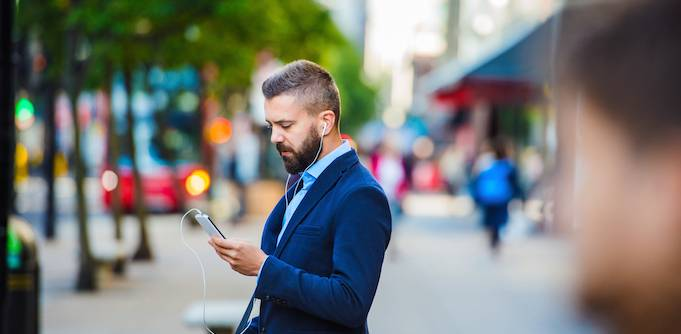 A man in business suit with earphones on and looking at his phone