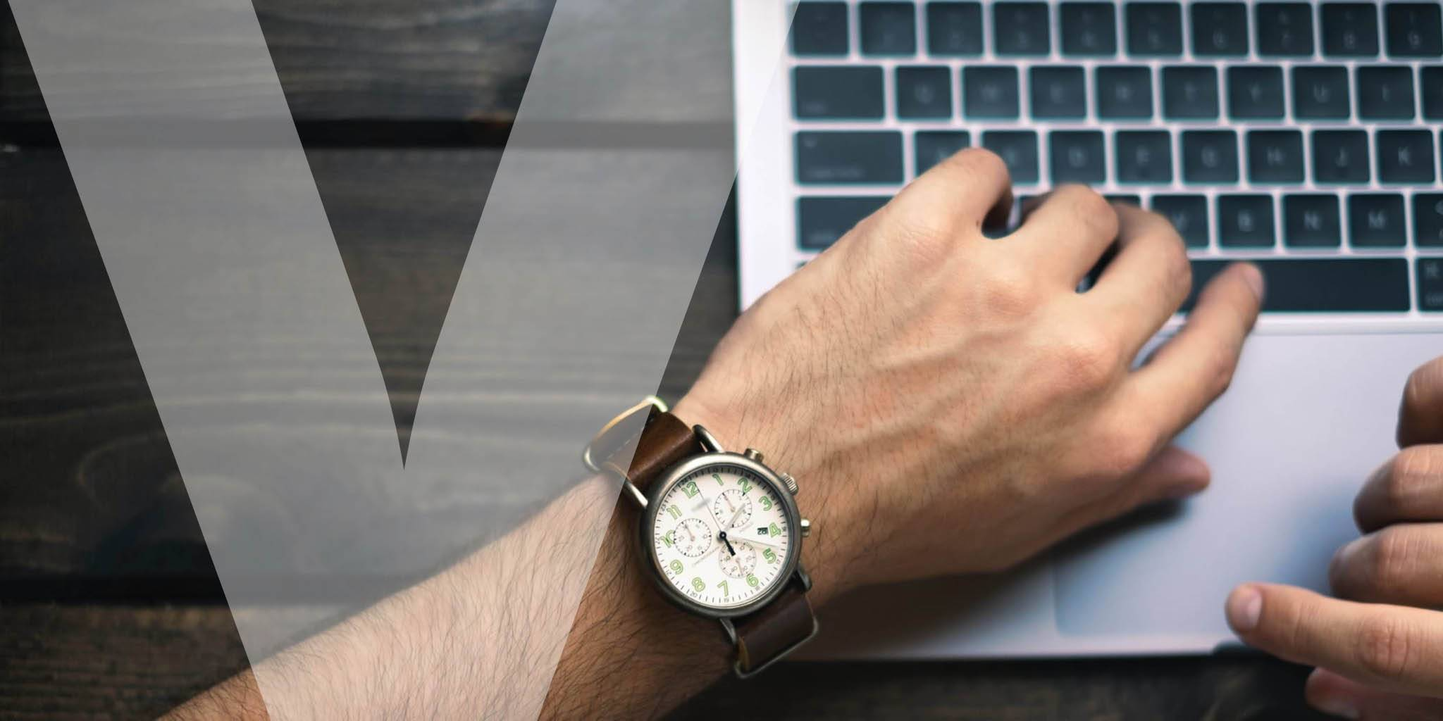 A hand with a wrist watch resting on a laptop